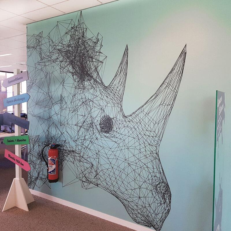 Décoration murale sur fond coloré d'un rhinocéros en lignes graphiques
