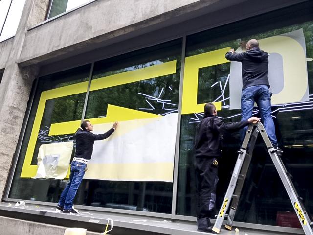 Installation d'un adhésif sur vitrine de magasin par des techniciens Paristic